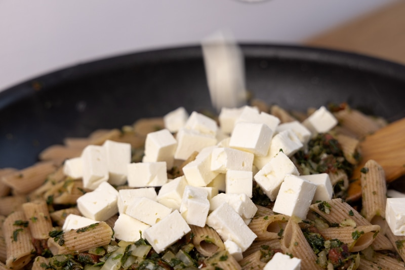 Adding feta cubes to pasta