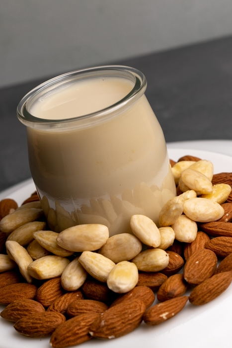Almon milk in a glass jar and almonds