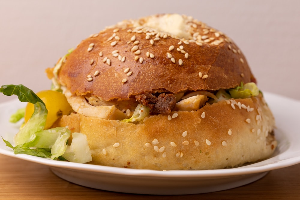 Bagel sandwich with lettuce, chicken, and sauce
