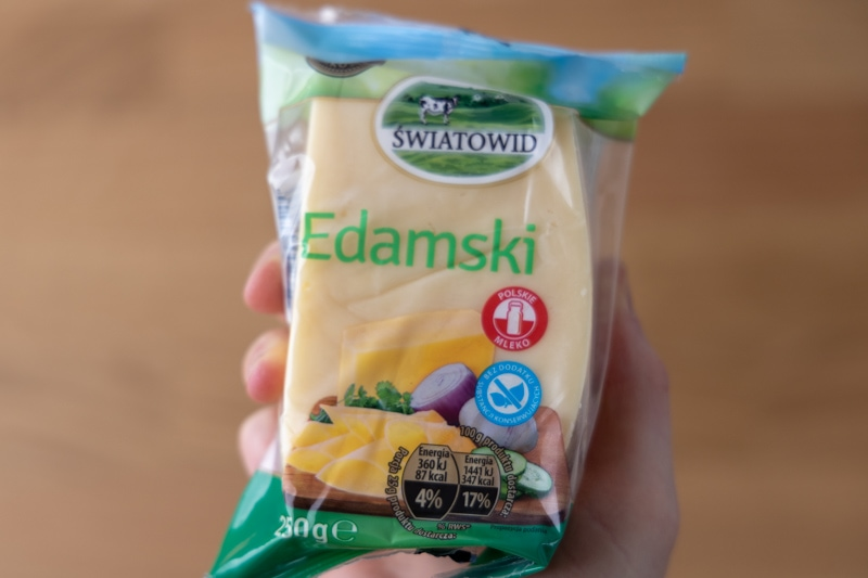 Block of Edam hard cheese in hand