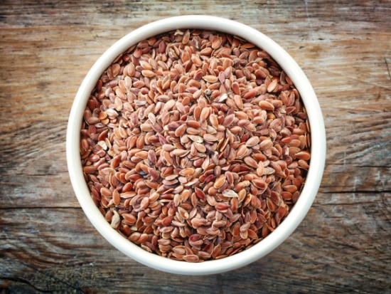 A bowl of flax seeds on a wooden table