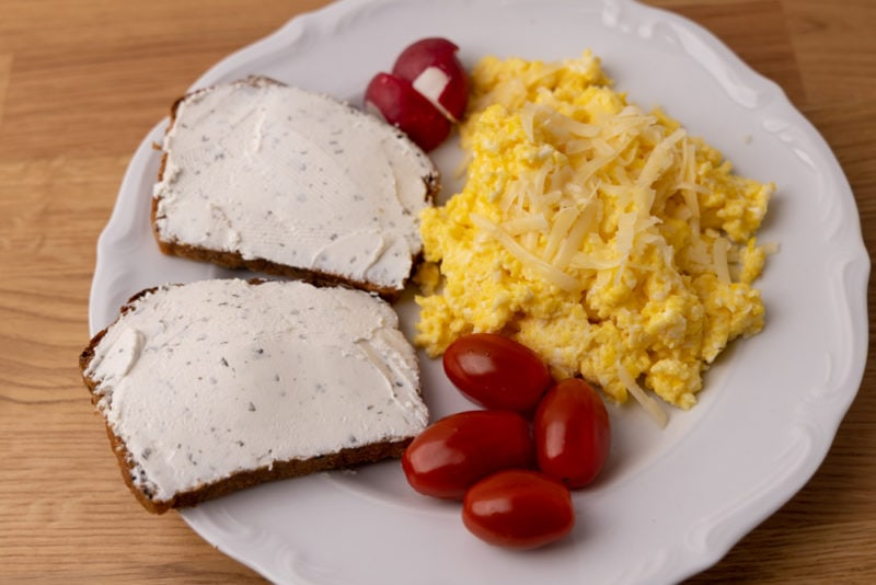 Bread with goat cheese and scrambled eggs