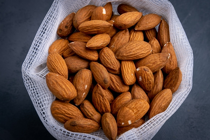 Bunch of unpeeled almonds in a mesh bag