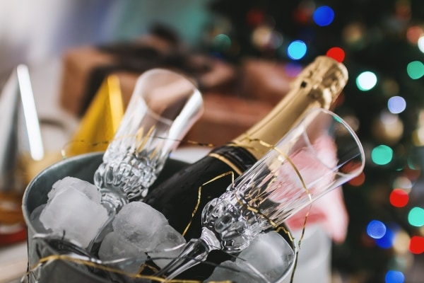 Bottle of champagne and two glasses in a bucket full of ice