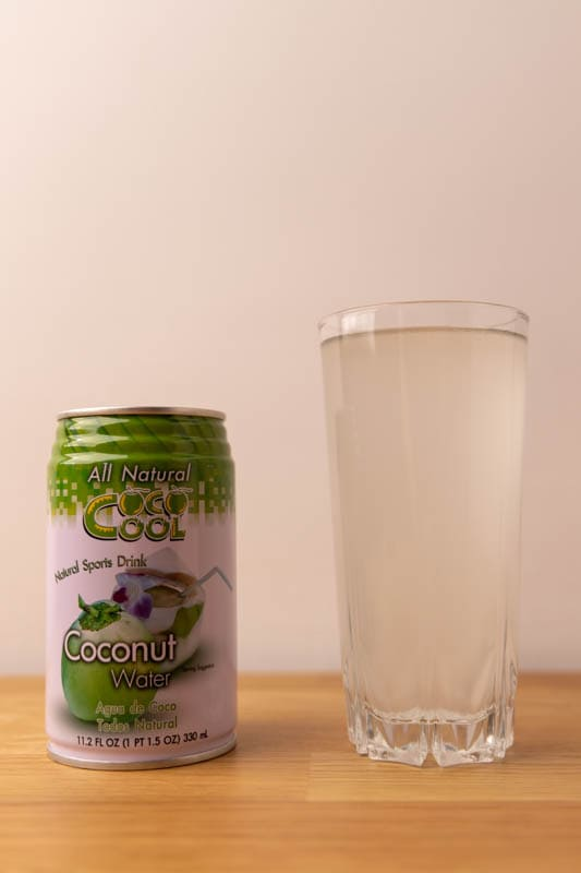 Coconut water: can and glass with liquid