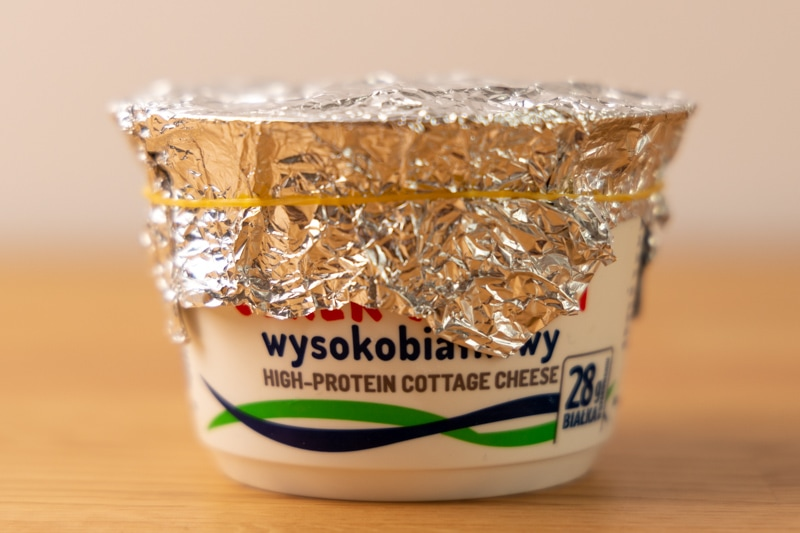 Cottage cheese wrapped with aluminum foil and a rubber band