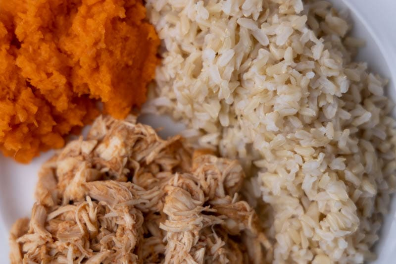 Dinner with BBQ chicken, rice, and grated carrots