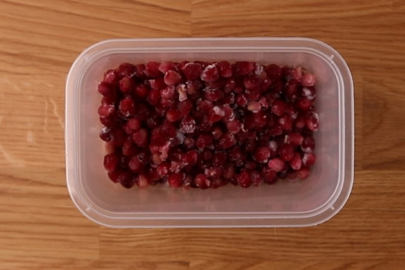 Frozen pomegranate seeds in a container