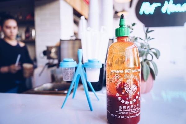 Half-full bottle of Sriracha sauce