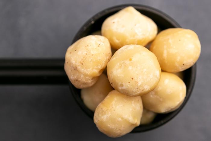 Macadamia nuts in a black scoop