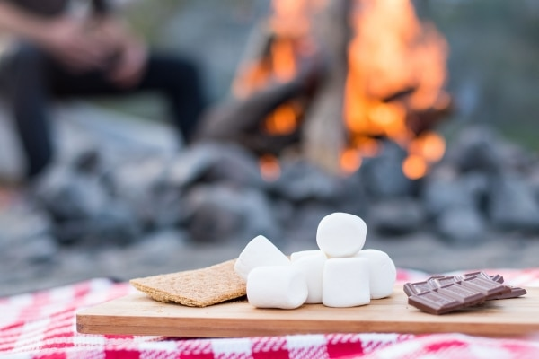 Marshmallows and chocolate on a wooden cutting board