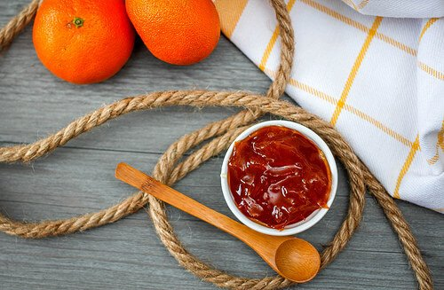 Orange jam with a wooden spoon