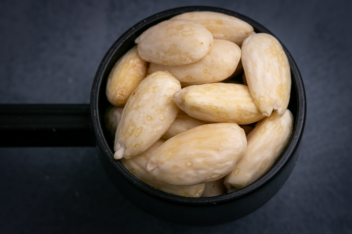 Peeled almonds in a scoop