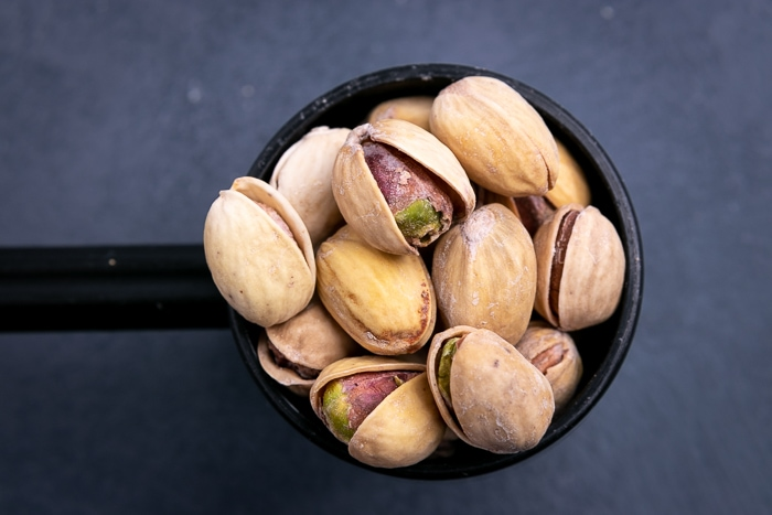 Pistachios in a black scoop