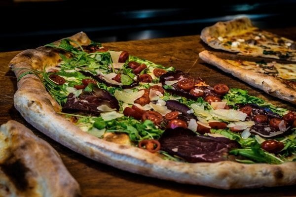 Pizzas sitting on a wooden table with different toppings.