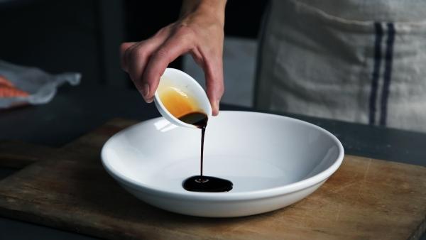 Pouring balsamic vinegar into a white bowl