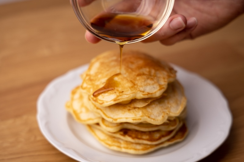 Pouring maple syrup over pancakes