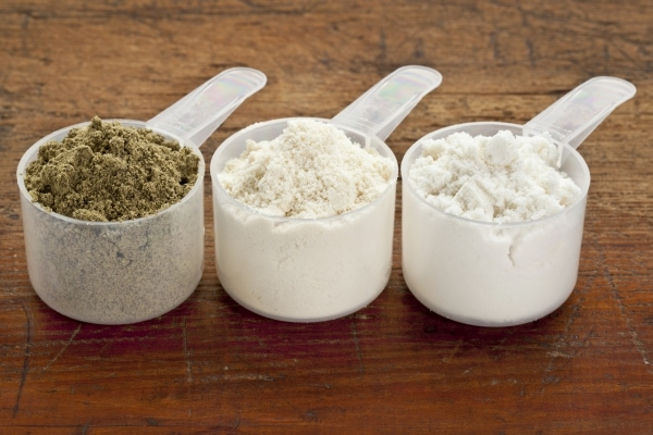 Scoops of three protein powders (from left hemp seed, whey concentrate, whey isolate)
