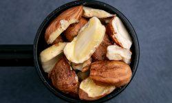 Shelled hazelnuts in a black scoop