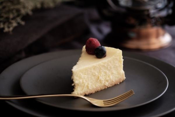 Slice of fruit-garnished cheesecake on a black plate