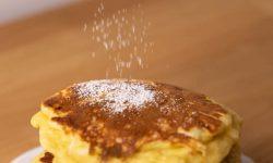 Sprinkling powdered sugar over pancakes