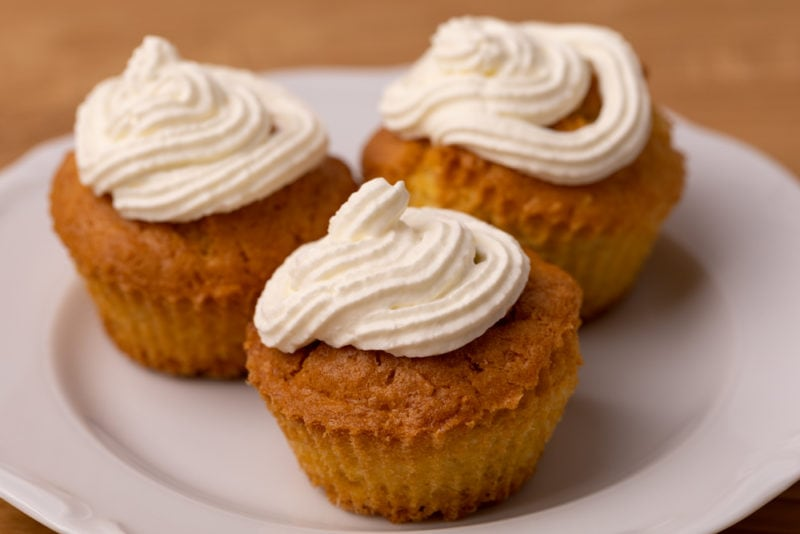 Three cupcakes frosted with whipped cream