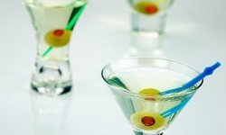 Three minature dirty martinis served with a traditional olive garnish