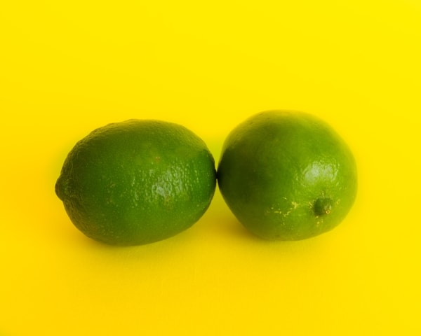 Two limes on yellow background