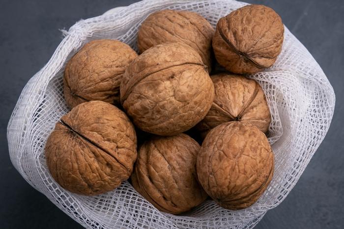 Unshelled walnuts in a mesh bag
