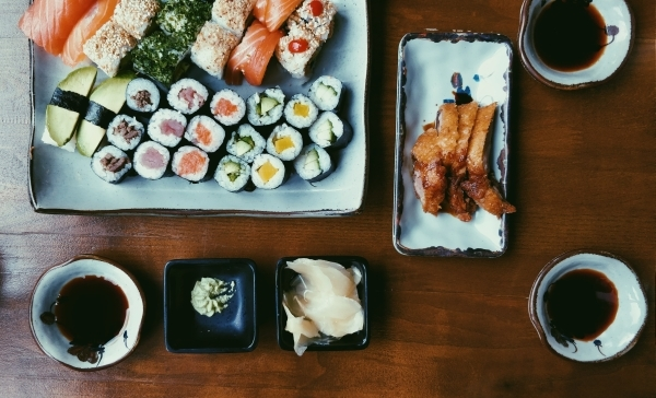 Variety of sushi, and three bowls of soy sauce